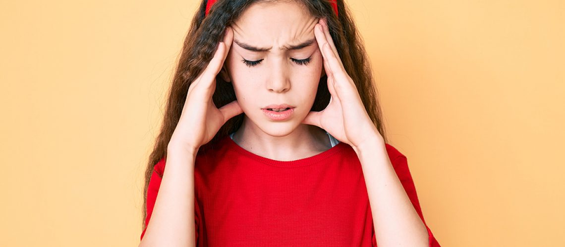 Cute hispanic child girl wearing casual clothes and diadem with hand on head for pain in head because stress. suffering migraine.